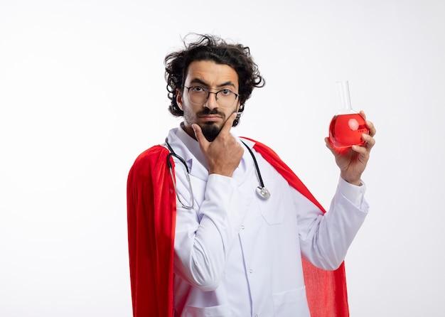 赤いマントと聴診器を首にかけた医者の制服を着た光学ガラスの思慮深い若い白人男性は、あごに手を置き、ガラスフラスコに赤い化学液体を保持します