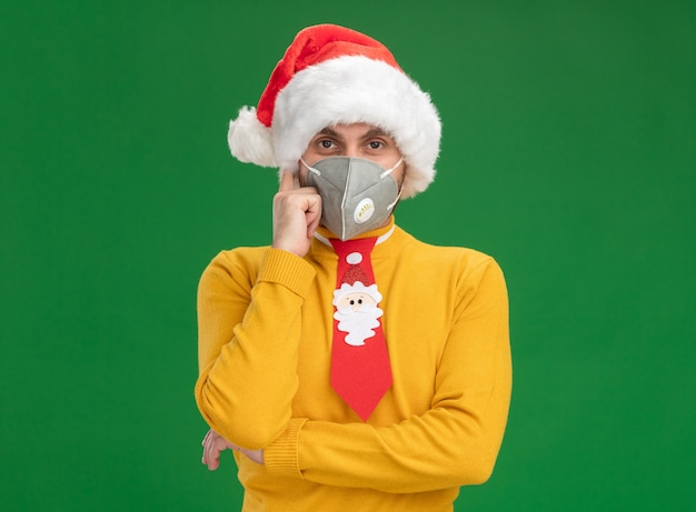 クリスマスの帽子をかぶって、コピースペースで緑の背景に分離された思考ジェスチャーをしているカメラを見て保護マスクとネクタイの思いやりのある若い白人男性