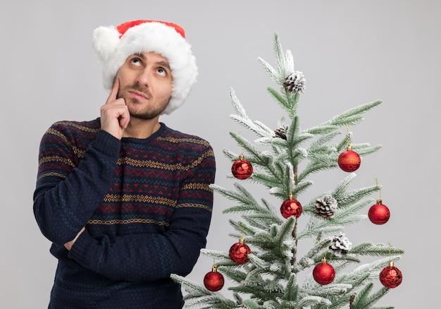 크리스마스 트리 근처에 서있는 크리스마스 모자를 쓰고 사려 깊은 젊은 백인 남자는 흰색 배경에 고립 된 감동 얼굴을 찾고