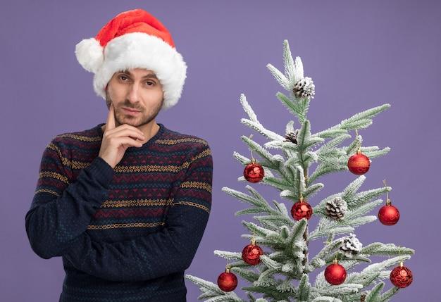 Riflessivo giovane uomo caucasico indossando il cappello di natale in piedi vicino all'albero di natale decorato tenendo la mano sul mento guardando la telecamera isolata su sfondo viola