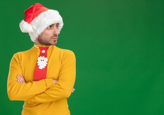 Riflessivo giovane uomo caucasico indossando il cappello di natale e cravatta in piedi con la postura chiusa guardando lato isolato su sfondo verde con copia spazio
