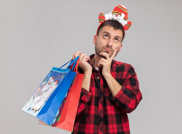 白い背景で隔離のあごに手を保ちながら見上げるクリスマスギフトバッグを保持しているクリスマスのヘッドバンドを身に着けている思いやりのある若い白人男性