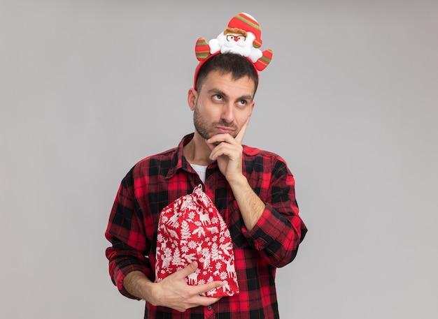 Riflessivo giovane uomo caucasico indossando la fascia di natale tenendo il sacco di natale tenendo la mano sul mento cercando isolato su sfondo bianco con spazio di copia