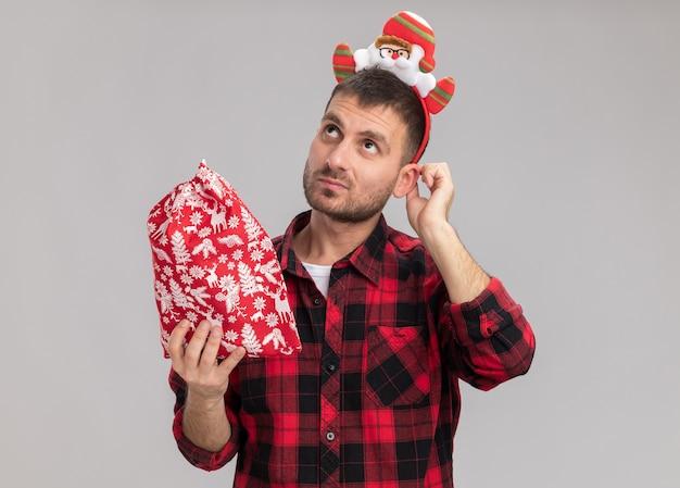 Riflessivo giovane uomo caucasico indossando la fascia di natale tenendo il sacco di natale toccando l'orecchio cercando isolato su sfondo bianco
