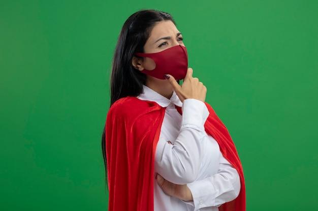 Riflessivo giovane supereroe caucasico ragazza in piedi in vista di profilo che indossa la maschera mettendo la mano sul gomito e sul mento guardando l'angolo isolato su sfondo verde con spazio di copia