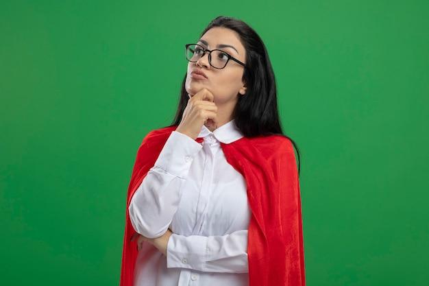 Giovane ragazza caucasica premurosa del supereroe con gli occhiali che tiene la mano sul gomito e sul mento che guarda dritto isolato sulla parete verde con lo spazio della copia