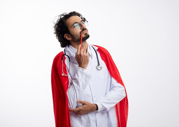 赤いマントと聴診器を首にかけた医者の制服を着た光学ガラスの思慮深い若い白人のスーパーヒーローの男は、白い壁で隔離された側を見て彼の唇に鉛筆を置きます