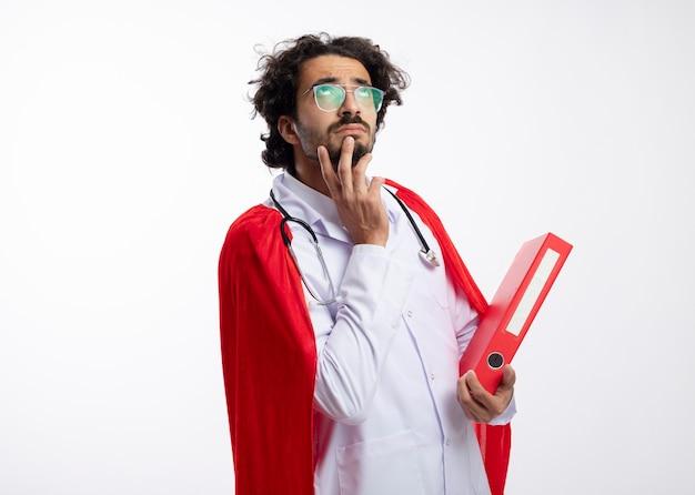 Uomo premuroso giovane supereroe caucasico in occhiali ottici che indossa l'uniforme del medico con mantello rosso e con lo stetoscopio intorno al collo mette la mano sul mento e tiene la cartella di file con lo spazio della copia