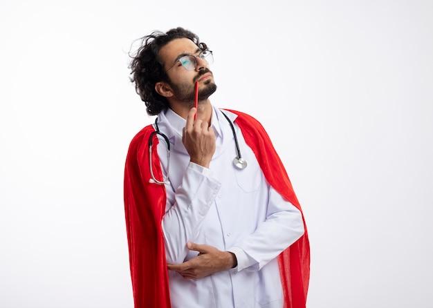 Uomo premuroso giovane supereroe caucasico in vetri ottici che indossa l'uniforme del medico con mantello rosso e con lo stetoscopio intorno al collo mette la matita sul labbro guardando il lato isolato sul muro bianco