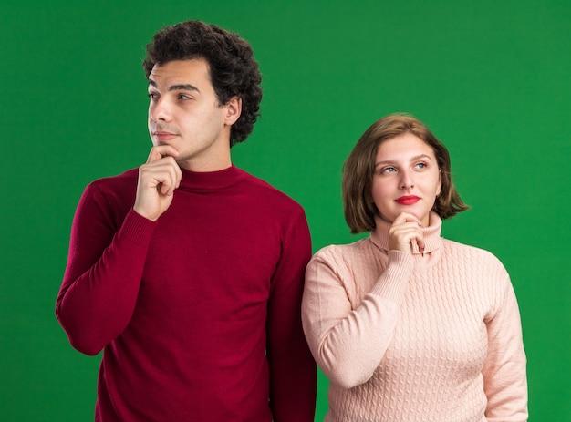 緑の壁で隔離された側を見ているあごに手を置いている思いやりのある若いカップル
