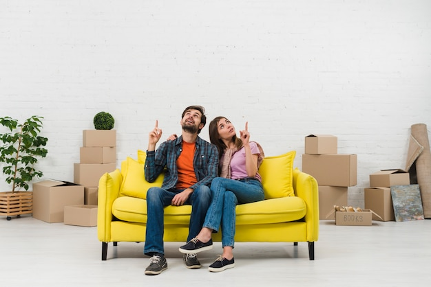 Thoughtful young couple sitting on yellow sofa pointing the finger upward in new home