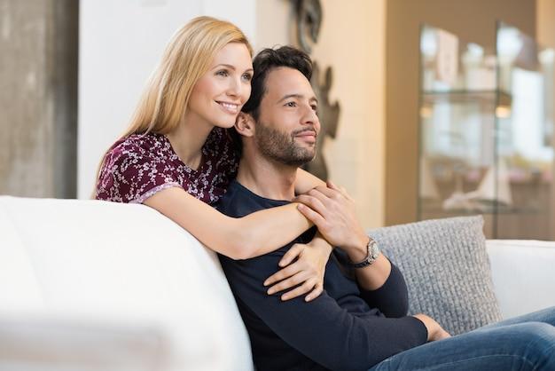 思いやりのある若いカップルがリビングルームのソファでリラックスしながら笑っています。