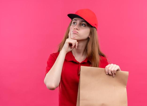 Premurosa giovane ragazza di consegna in uniforme rossa che tiene il sacchetto di carta e mettendo la mano sotto il mento sulla parete rosa isolata con lo spazio della copia