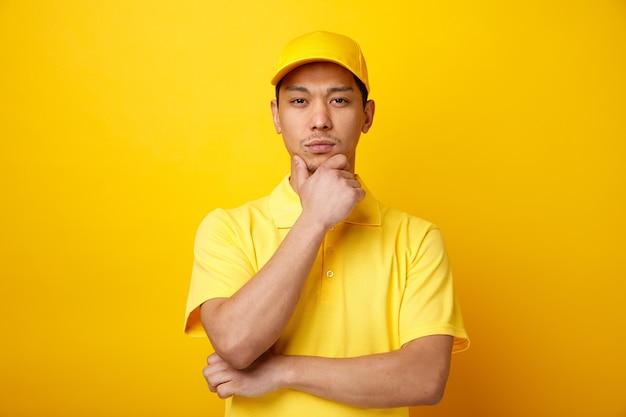 Considerato giovane uomo di consegna che indossa il cappello e uniforme tenendo la mano sul mento