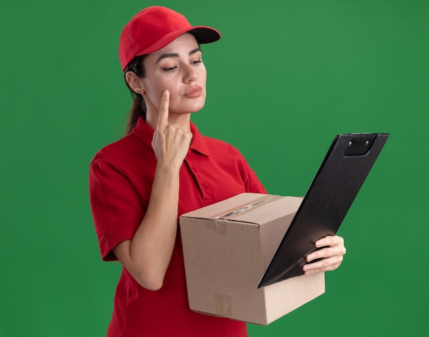 制服とキャップを保持しているカードボックスとクリップボードを頬に指を置いてクリップボードを見ている思いやりのある若い配達の女性