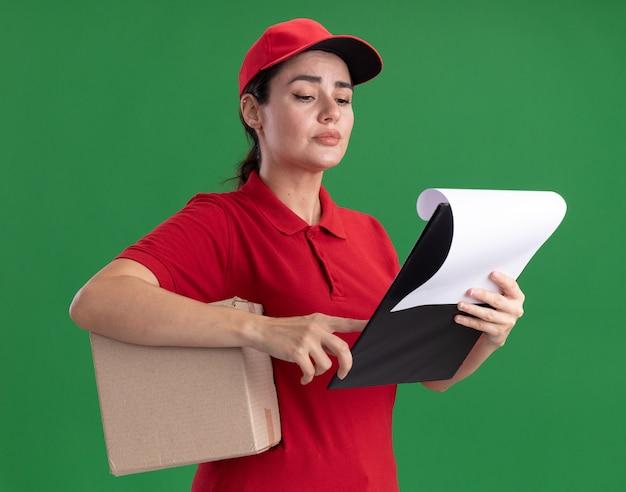 Premurosa giovane donna delle consegne in uniforme e cappuccio che tiene scatola di cartone e appunti guardando gli appunti che puntano il dito su di esso