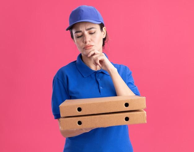 Premurosa giovane donna delle consegne in uniforme e berretto che tiene e guarda i pacchetti di pizza toccando il mento isolato sulla parete rosa con copia spazio