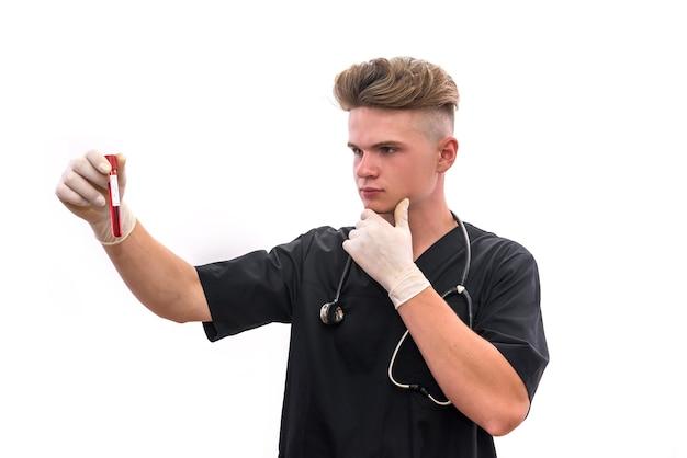 赤い試験管を見ている思いやりのある若い医者。彼はそれを白い背景で隔離して保持しています