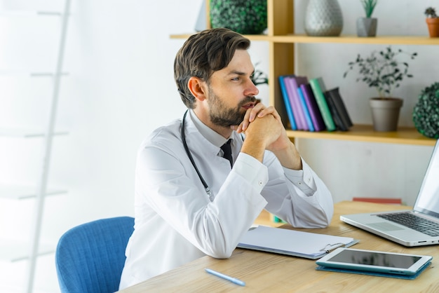 Thoughtful young doctor in office
