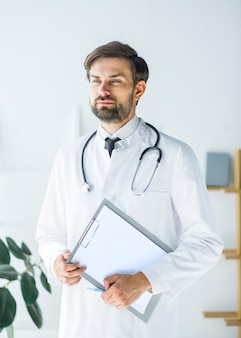 Thoughtful young doctor with clipboard