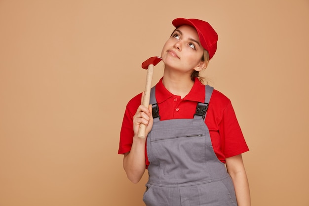 사려 깊은 젊은 여성 건설 노동자 모자와 유니폼을 입고 망치를 찾고 얼굴을 만지고