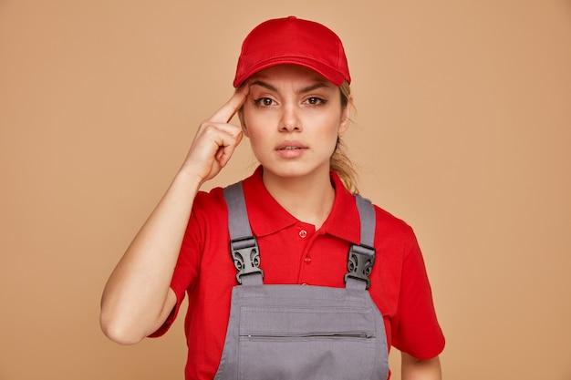 유니폼을 입고 사려 깊은 젊은 여성 건설 노동자와 생각 제스처를 하 고 모자
