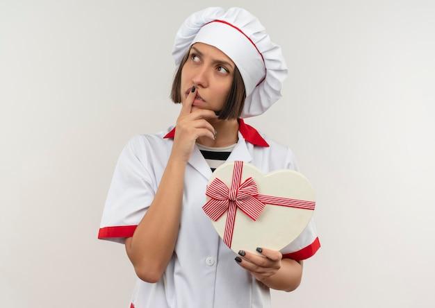 Giovane cuoco femminile premuroso in uniforme del cuoco unico che tiene il contenitore di regalo a forma di cuore che esamina lato con il dito sulle labbra isolate sulla parete bianca