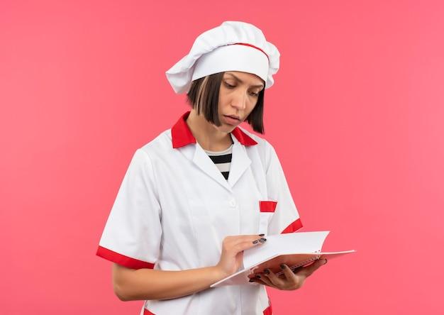 Задумчивая молодая женщина-повар в униформе шеф-повара держит и смотрит на блокнот, изолированный на розовой стене