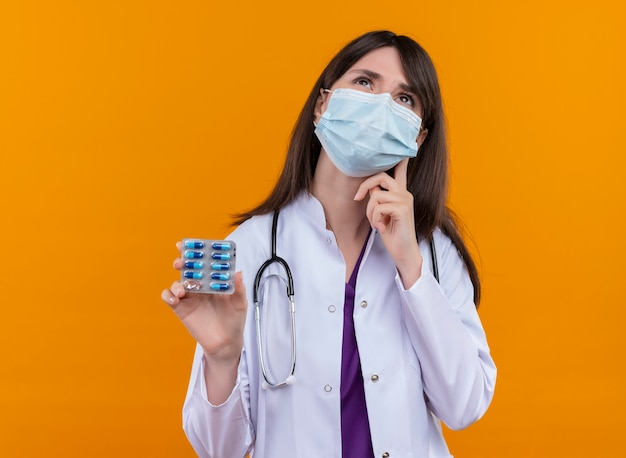 Thoughtful young female doctor in medical robe with stethoscope wears disposable medical face mask holds medicine on isolated orange background with copy space