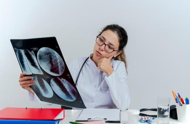 의료 가운과 청진 기 및 의료 도구를 들고 책상에 앉아 안경을 착용하는 사려 깊은 젊은 여성 의사가 고립 된 턱에 손을 넣어 엑스레이 촬영을보고