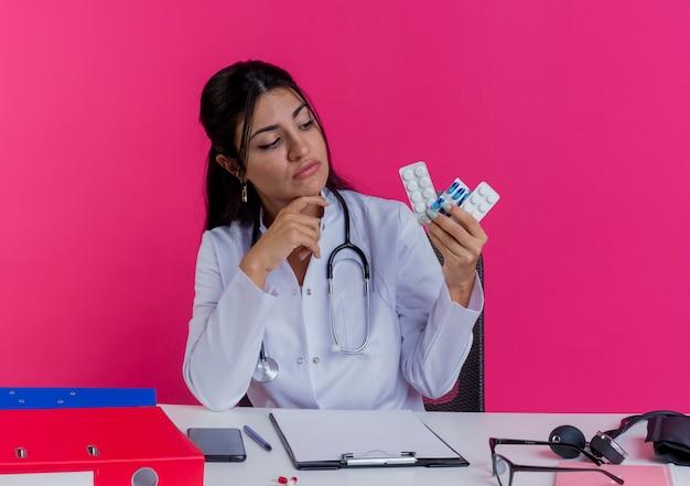 Задумчивая молодая женщина-врач в медицинском халате и стетоскопе сидит за столом с медицинскими инструментами, держа и глядя на медицинские препараты, касаясь подбородка, изолированного на розовой стене