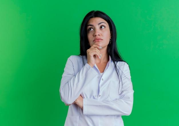 턱을 만지고 측면을보고 의료 가운을 입고 사려 깊은 젊은 여성 의사