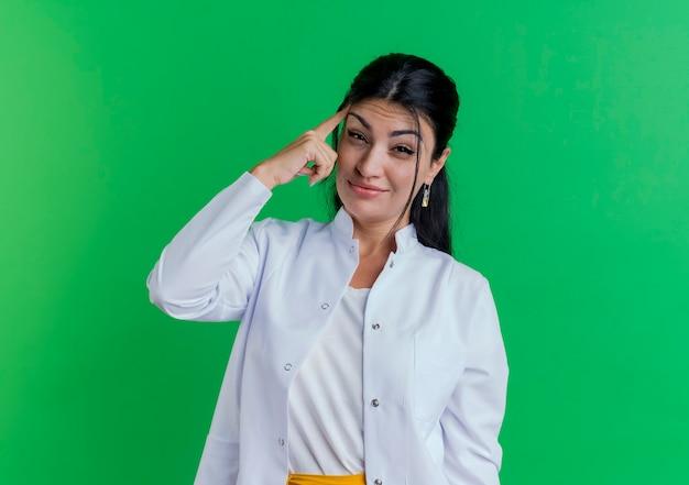 寺院に人差し指を探している医療ローブを着ている思いやりのある若い女性医師