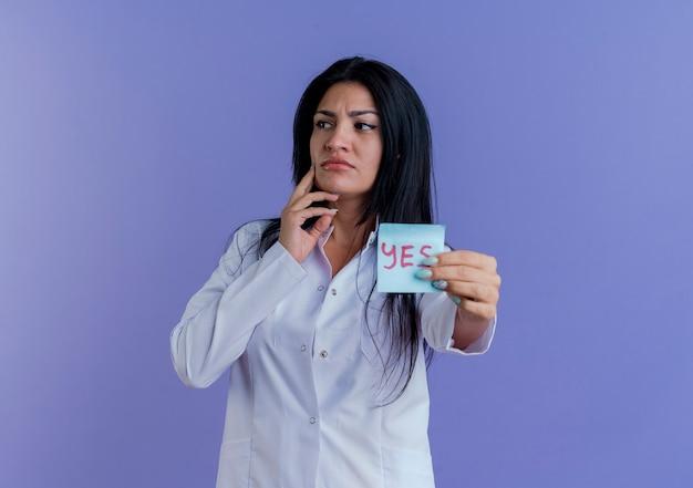 コピースペースで紫色の壁に分離された顔に触れる側を見てはいメモを示す医療ローブを身に着けている思いやりのある若い女性医師