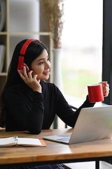 Заботливая молодая женщина слушает музыку в наушниках и пьет кофе.