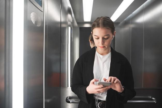 Вдумчивый молодой женский офисный работник использует свой смартфон