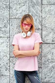 Thoughtful young female in stylish pink sunglasses with headphones on neck dressed in sporty t shirt and pants standing with arms crossed against gray stone wall