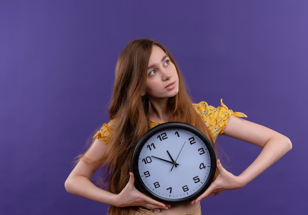 Giovane ragazza premurosa che tiene orologio e guardando il lato destro sulla parete viola isolata
