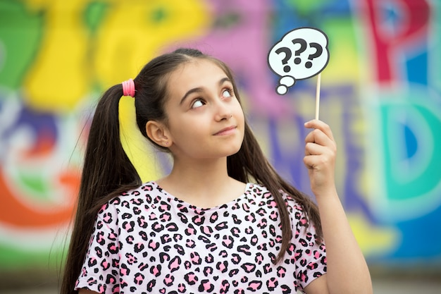 Thoughtful young girl holding up question marks