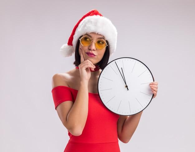 サンタの帽子と白い背景で隔離の側を見ているあごに手を置いて時計を保持しているメガネを身に着けている思いやりのある若い女の子