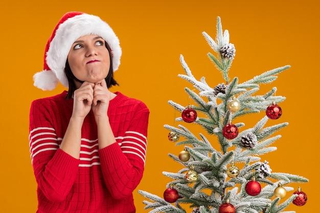 サンタの帽子をかぶった思いやりのある少女は、オレンジ色の壁に隔離されたすぼめた唇で顎の下に手を保ちながら飾られたクリスマスツリーの近くに立っています