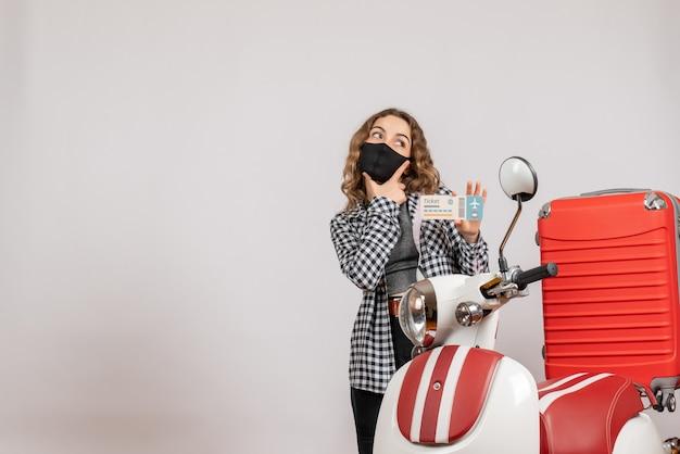 Premurosa ragazza con maschera in piedi vicino al motorino con la valigia