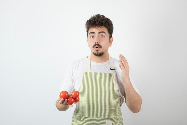Задумчивый молодой парень держит кучу помидоров и поднимает руку.