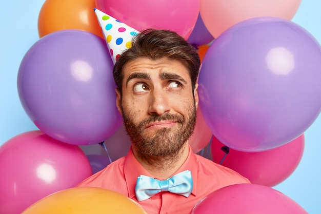 Thoughtful young guy posing surrounded by birthday colorful balloons