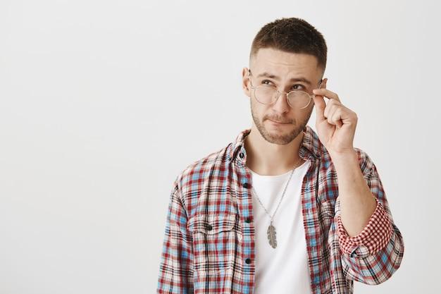Giovane ragazzo premuroso con gli occhiali in posa