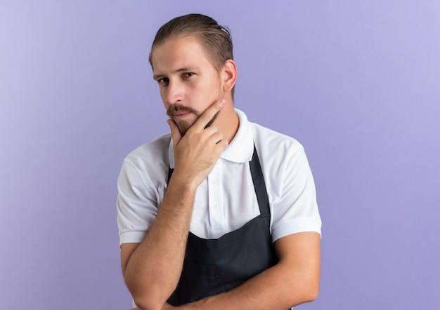 Riflessivo giovane barbiere bello indossando l'uniforme toccando il mento e mettendo la mano sotto il gomito isolato sulla parete viola
