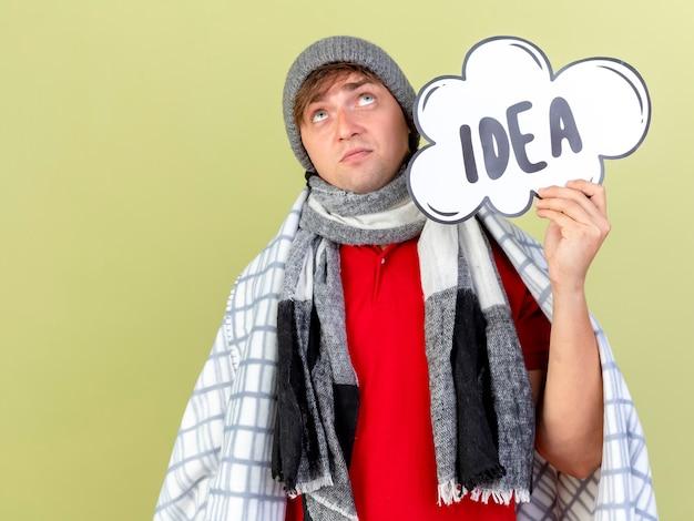 冬の帽子とスカーフを身に着けている思いやりのある若いハンサムな金髪の病気の男は、コピースペースでオリーブグリーンの背景に分離された見上げるアイデアバブルを保持している格子縞に包まれています