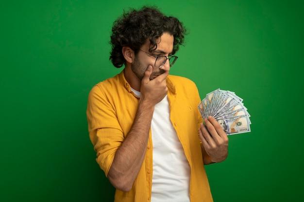 Задумчивый молодой красивый кавказский мужчина в очках держит и смотрит на деньги, держа руку за рот, изолированную на зеленом фоне с копией пространства