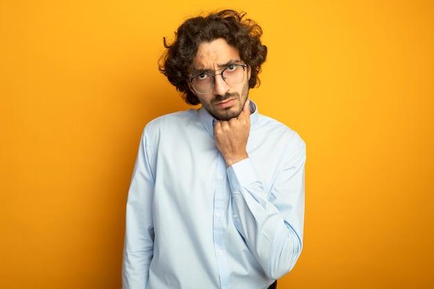 Задумчивый молодой красивый кавказский мужчина в очках смотрит в камеру, кладя руку под подбородок, изолированную на оранжевом фоне с копией пространства