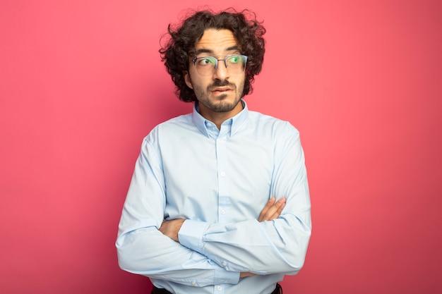 コピースペースで深紅色の背景に分離された唇を噛む側を見て閉じた姿勢で立っている眼鏡をかけて思慮深い若いハンサムな白人男性